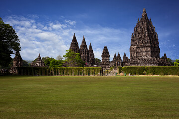 Prambanan Hindu Temple view in Yogyakarta, Java Island, Indonesia, its most beautiful Hindu temple in Indonesia. View with blue sky background and green grass garden foreground