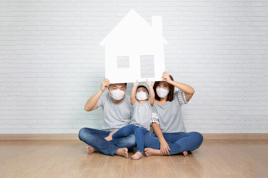 Asian family wearing protective mask for prevent virus and holding paper home, New house and real estate concept
