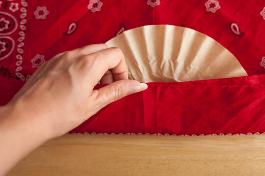 A woman folds a bandanna over coffee filter to make a DIY face covering, this project is recommended by the CDC to protect from coronavirus when out for essential services like groceries. Shallow DOF.