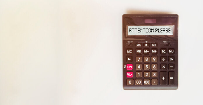 black calculator with text ATTENTION PLEASE on the white background