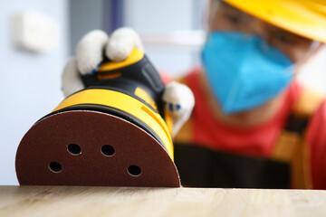 Masked carpenter grinds wood with sander machine