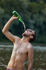 Man pouring drink into open mouth from bottle