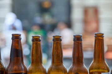 Beer bottles on a bar terrace, blurry blurred people talking in the background