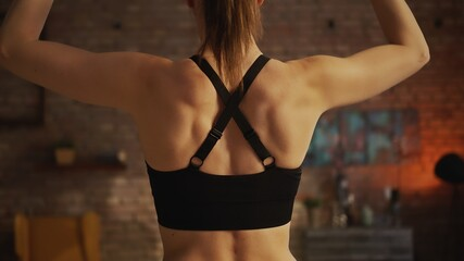 Back of young muscular woman doing workout. . Woman doing barbell exercise at home.