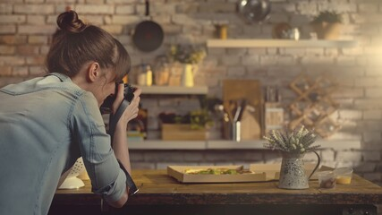 Woman photographing take away pizza on the kitchen table at home.