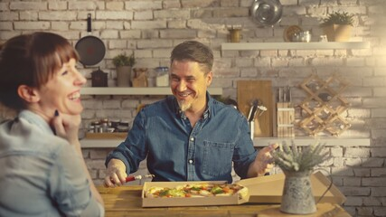 Laughing couple eating take away pizza from food box. Man slicing pizza on kitchen table at home.