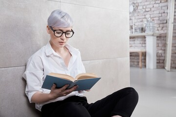 Young woman in retro style sitting on floor at home, reading a book.