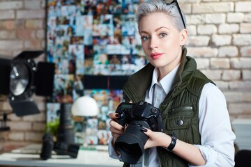 Portrait of attractive young female photographer holding camera, looking at camera.
