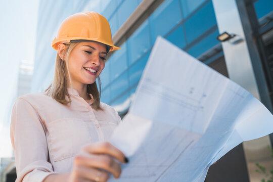 Professional architect holding blueprints outdoors.