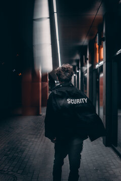 male with a security jacket walk in night street