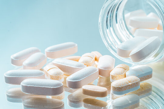 White and yellow tablets or pills or medication or drugs with bo
