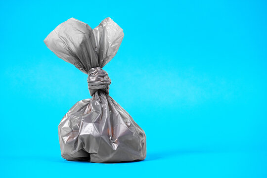 Close up plastic bag gathering with dog poop droppings on a blue background. Eco friendly solution for pet owners