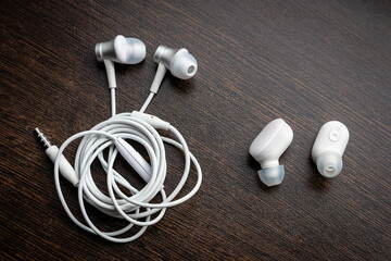 white wireless bluetooth headphones and wired tangled headphones close-up