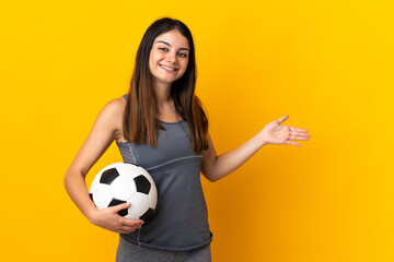 Young football player woman isolated on yellow background extending hands to the side for inviting to come