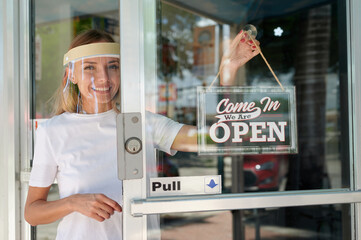 Woman in white shirt wearing face shield hanging open sign for storefront business on the door