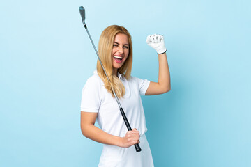 Young Uruguayan blonde woman over isolated blue background playing golf and celebrating a victory