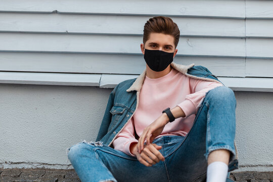 Trendy model young man in stylish denim jacket in torn fashionable blue jeans in fashion black mask sit on stone tile near vintage wall in city. Attractive guy in trendy casual clothes on street.