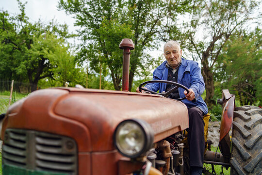 Senior man farmer sitting on old tractor - pensioner driving ancient rusty tractor in nature on farm working in the field in day front view - real people retirement self sufficiency concept