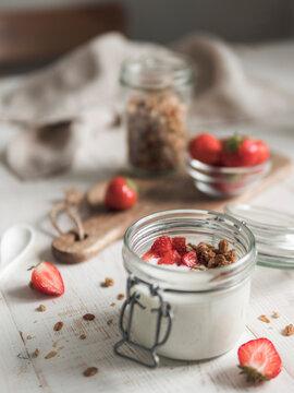 Kefir or yogurt served granola and strawberries