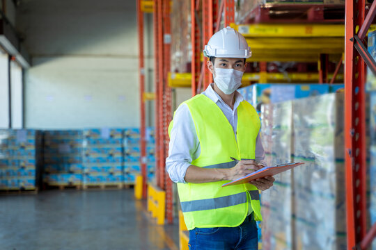 Worker working wearing protective mask to Protect Against Covid-19 working and checking product in a large warehouse.