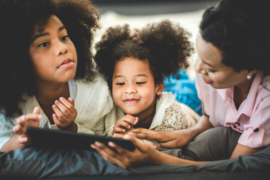 Happy American African family watching tablet on bed at home, The concept of families of all ages is enjoying the activities in the house.