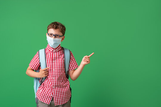 schoolboy in protective mask, standing against background of a green Board.