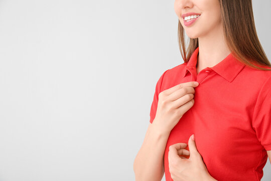 Beautiful young woman in stylish polo shirt on light background