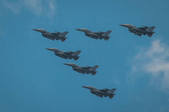 Modern fighter aeroplanes flying in the V formation over the blue skies.
