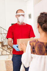 Deliveryman wearing protection mask holding package for female customer.