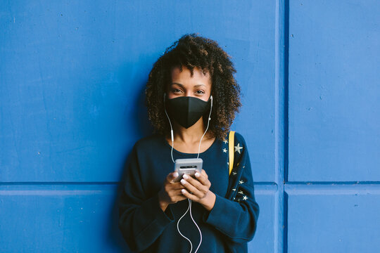 Portrait of urban afro hairstyle woman wearing face mask and using her phone for listening music. Coronavirus Covid-19 new lifestyle.