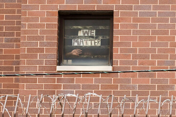 "An inmate holds a sign to his cell window reading ""We Matter"" at Cook County Jail"