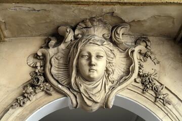 Tête de femme sculptée en pierre sur une façade ancienne. Paris.