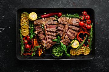 Barbecue. Steak on the bone with grilled vegetables and spices. T-bone steak. Top view. Rustic...
