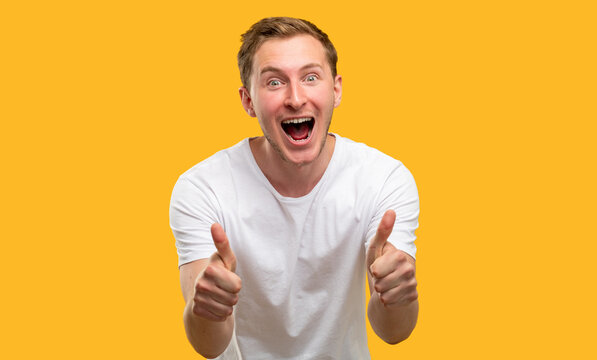 Like gesture. Approval admiration. Excited man supporting with thumbs up isolated on orange background.