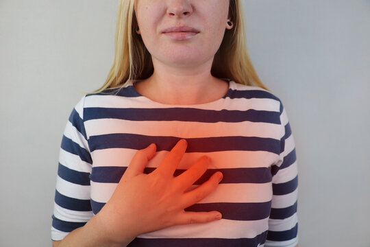 A woman grabs his chest in the region of the heart. Heart attack or chest pain. The concept of heart disease and its pain manifestations.