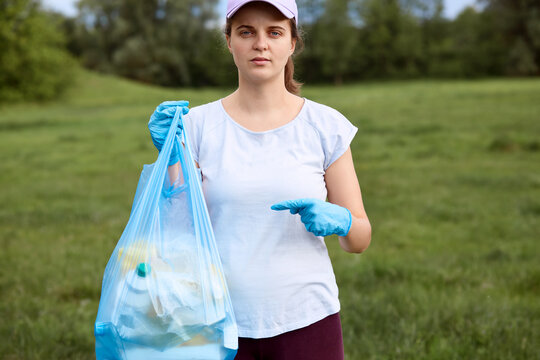 Serious female in baseball cap and t shirt, lady with garbage bag in one hand looking at camera with confident facial expression pointing at litter bag, posing in meadow, cleaning field.