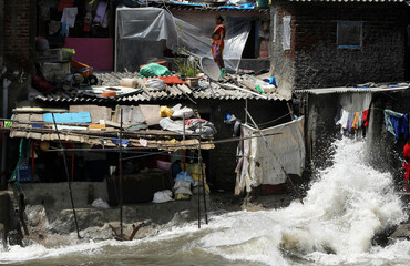 Woman standing on the roof of a house watches as waves crash along a seafront during high tide in Mumbai