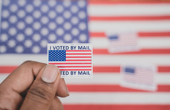 Holding I voted my mail sticker in hands with US flag as background - concept of voted through mail during election