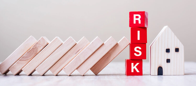 Red RISK cube blocks stop falling blocks protect house miniature. fall Business, Home Insurance, investment, Crisis, Economic recession, Developer, Real Estate and Property concept