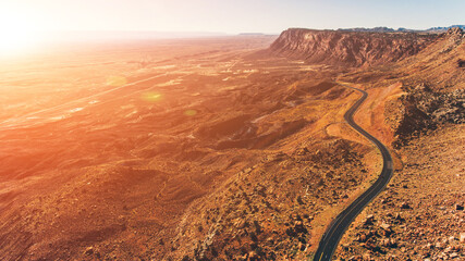 Fototapeten Ziegel Aerial view of beautiful rocky mountain range with an asphalt road highway running along. Bird's eye scenery view red cliff in area of desert landscape of United states