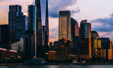 Fotomurales - Panoramic view of Manhattan Island with sunset reflection in glass buildings.Scenery skyline view of contemporary skyscrapers of downtown financial district in New York. Gold sunset over NYC cityscape