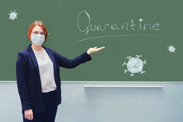 School teacher in a medical mask points to a blackboard with the words