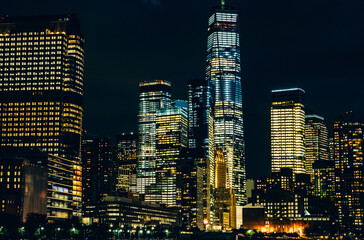 Fotomurales - Scenery view of Lower Manhattan skyline at night time with city lights in windows. Beautiful cityscape view of New York downtown. Contemporary metropolis city in need of a huge amount of electricity