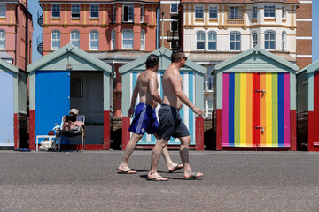 Men walk past a woman sunbathing in front of beach huts in Brighton