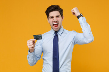 Screaming young business man in classic blue shirt tie posing isolated on yellow background. Achievement career wealth business concept. Mock up copy space. Hold credit bank card doing winner gesture.