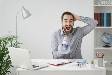 Amazed young business man in gray shirt sit at desk work on laptop pc computer in light office on white wall background. Achievement business career concept. Screaming in megaphone put hand on head.