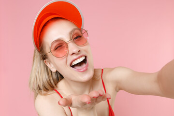 Close up of blinking young woman girl in red one-piece swimsuit cap eyeglasses isolated on pink background studio. People summer vacation rest lifestyle concept. Doing selfie shot on mobile phone.