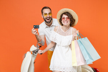 Cheerful couple friends guy girl in summer clothes hat glasses sit on moped isolated on orange background. Driving motorbike transportation concept. Hold package bag with purchases credit bank card.