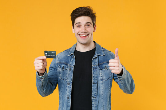 Cheerful young man guy 20s in casual denim jacket posing isolated on yellow wall background studio portrait. People lifestyle concept. Mock up copy space. Holding credit bank card, showing thumb up.