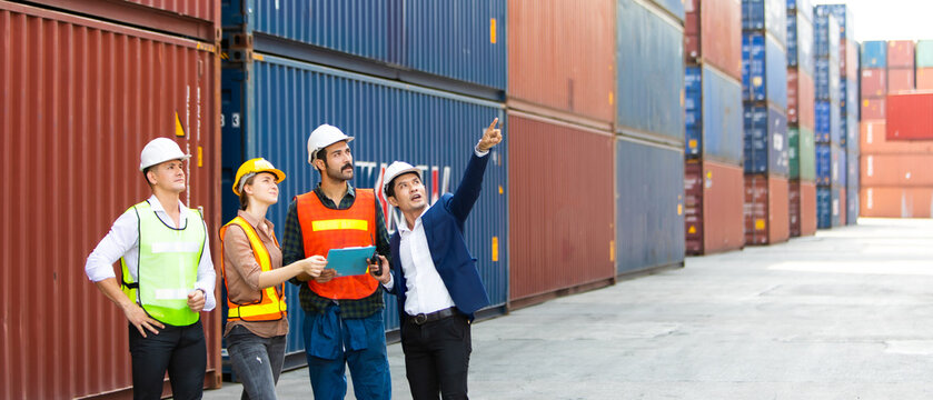 Group of professional dock worker and engineering people wearing hardhat safety helmet and safety vest standing and working at container yard port of import and export. Business teamwork concept
